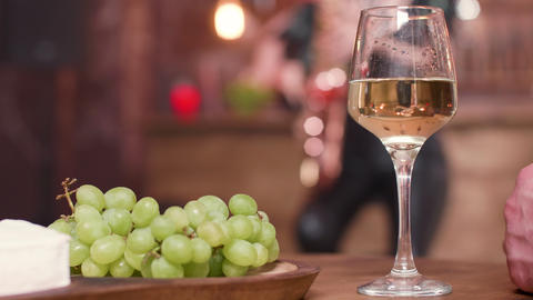 A glass of white wine and grapes on a wooden table Footage