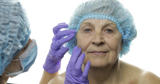 Smiling elderly female in protective hat. Plastic surgeon checking woman face Footage
