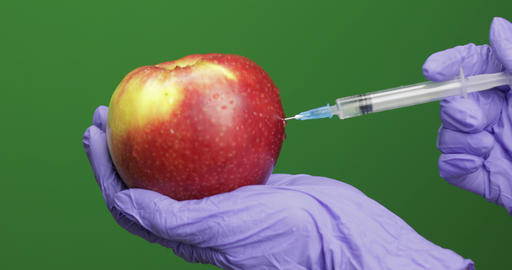 Female scientist makes a injection with a medicine syringe in apple Footage