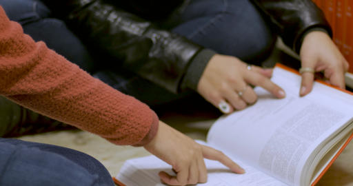Two young female students studying a textbook together while laughing in a library Archivo