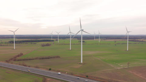 Wind turbines and agricultural fields on a summer day - Energy Production with Live Action