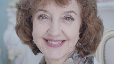 Close up portrait cute happy positive elegant mature lady sitting in the Footage