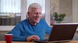 Closeup shoot of aged caucasian man typing on the laptop smiling happily indoors Footage