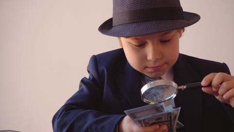 Child boy looks like a businessman in hat and suit is looking at dollars with Live Action