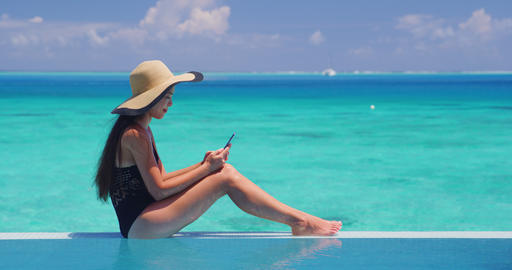 Phone - woman using mobile cell phone app on vacation sitting af pool Footage