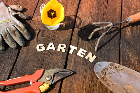 Top view of gardening stuff and german letters garden on wooden background Photo