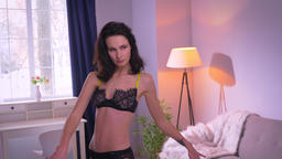 Joyful and active brunette model in black lingerie dancing actively in cozy home Footage