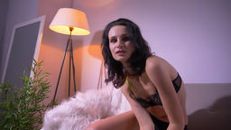 Portrait of tender brunette model in black lingerie posing sexually on sofa and Footage