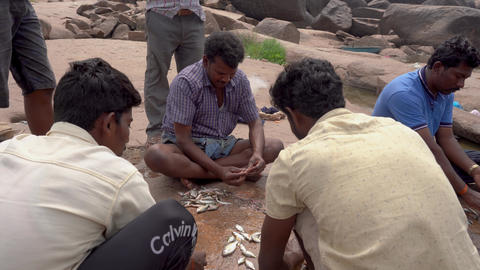 Fishermen are cleaning fish by the river Archivo