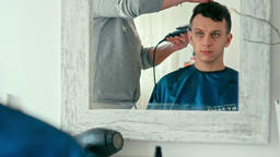 Barber Makes Haircut by Clipper. Man in Barbershop Salon. Reflection in Mirror Footage