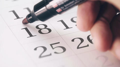 Drawing red circled mark on the eighteenth 18 day of a month in the calendar Live Action