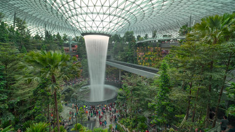 time lapse clip of Tourists enjoying rain vortex attraction in Changi Jewel airport, Singapore Footage