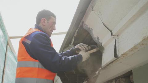 Man worker in orange uniform and helmet detaches dirty old wooden wall Footage