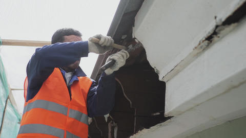 Asian male worker in orange vest breaks dirty old wooden wall with tools Footage