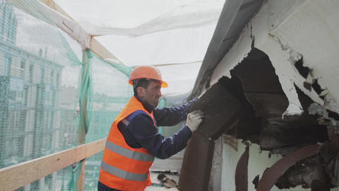 Construction asian laborer in orange safety outfit breaks dirty old wooden wall Footage