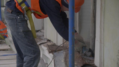 Construction worker uses cutting machine to cut old dust metallic part of wall Live Action