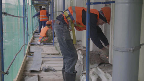 Construction worker uses power cutting machine during work on scaffolding Live Action