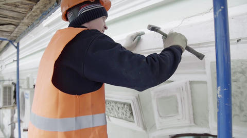 Worker with protective gloves uses small hammer for hitting piece of facade wall Footage