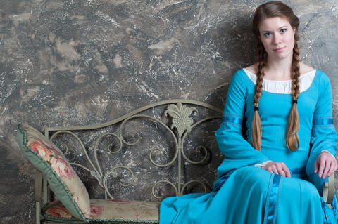Young girl in medieval dress sits on a banquette Photo