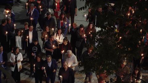 Elevated view of gathered people holding candles at night on Resurrection Sunday, called Pascha Live Action