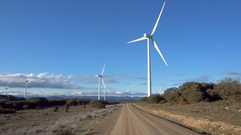 Pov walking toward large wind turbine on a sunny day Live Action