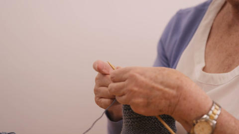 Senior woman knitting a wool Live Action