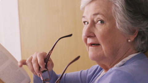 Senior woman removing spectacles and smiling Live Action