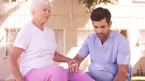 Male nurse assisting senior woman to exercise in the backyard Live Action