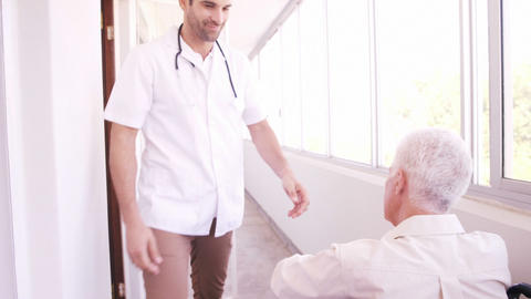 Male doctor assisting senior man on wheelchair Live Action