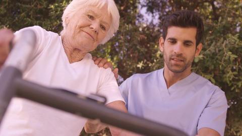 Male nurse assisting a senior woman to walk in the backyard Footage