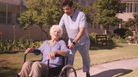 Male nurse assisting senior woman on wheelchair in the backyard Live Action