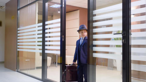 Child boy looks like a businessman in hat and suit is leaving his workplace in Live Action