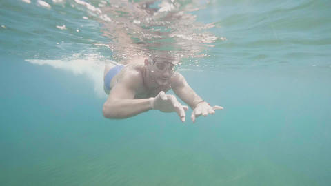 Man in mask is snorkeling in open ocean looking at wildlife, underwater shot Live Action