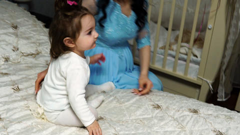 Little baby girl plays with a balloon sitting on the bed Archivo