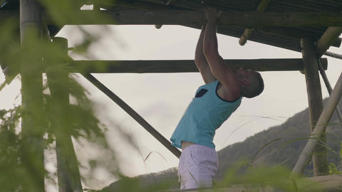 Sportsman training pull up exercise on horizontal bar on green mountain Live Action
