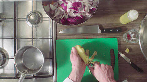 Chef peeling a ginger root on the chopping board Live Action