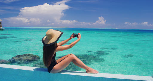 Phone - woman taking photo using mobile cell phone app on vacation by pool Footage
