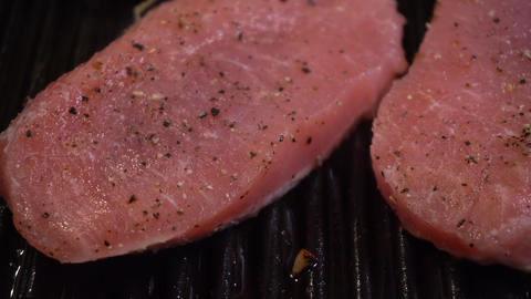 Close up of meat cooking on Cast-iron pan with heat wave and steam Archivo