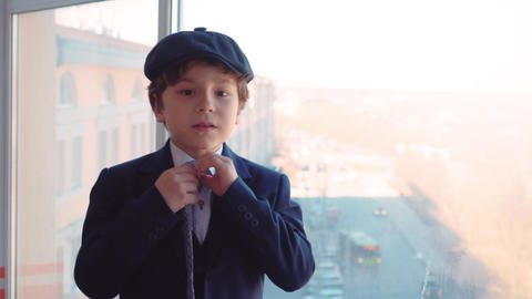 Portrait young boy in business suit straightens tie and cap in business office Live Action