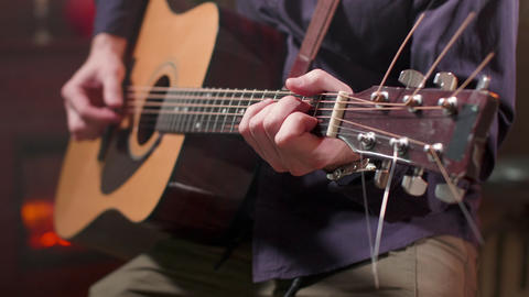 Male hands playing a song on an acoustic guitar Footage