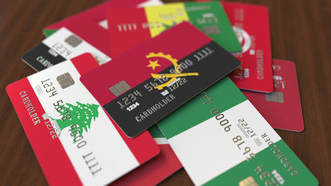 Many credit cards with different flags, emphasized bank card with flag of Angola Footage