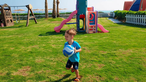 4k video of cheerful little boy running and playing with ball on th eplayground Footage