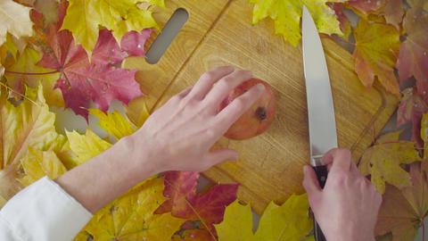 Autumn still life. Chef cutting a garnet Live Action