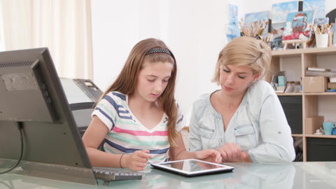 Teenage girl swiping the screen of a tablet while her mother looks at the screen Footage