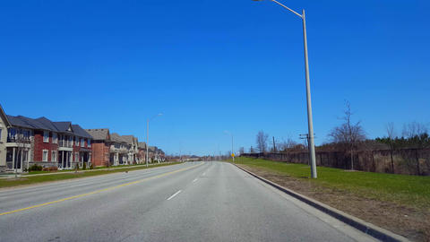 Driving Residential Road During Spring Day. Driver Point of View POV Along Beautiful Sunny Suburban Live Action