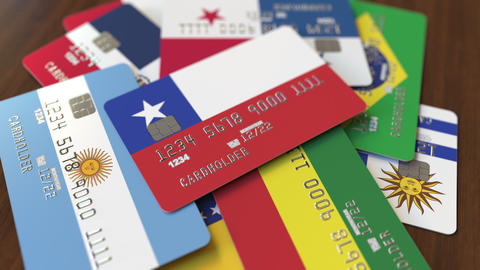 Many credit cards with different flags, emphasized bank card with flag of Chile Live Action