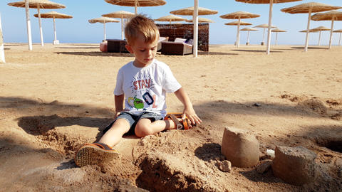 4k video of adorable toddler boy playing on the beach at sunny windy day Footage