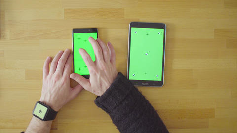 Three devices with green screens on the table Footage