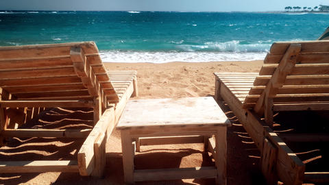 4k video of two wooden sunbeds on the beach. High waves rolling over the coast Live Action