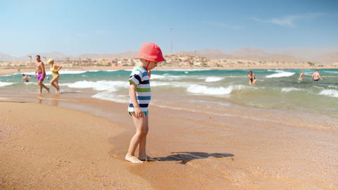 4k slow motion video of cheerful toddler boy standing on the sea shore and Footage